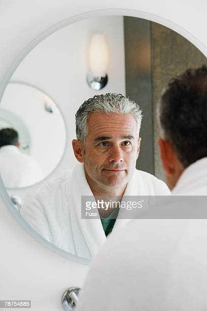 mature man looking in mirror - vanity mirror stock pictures, royalty-free photos & images