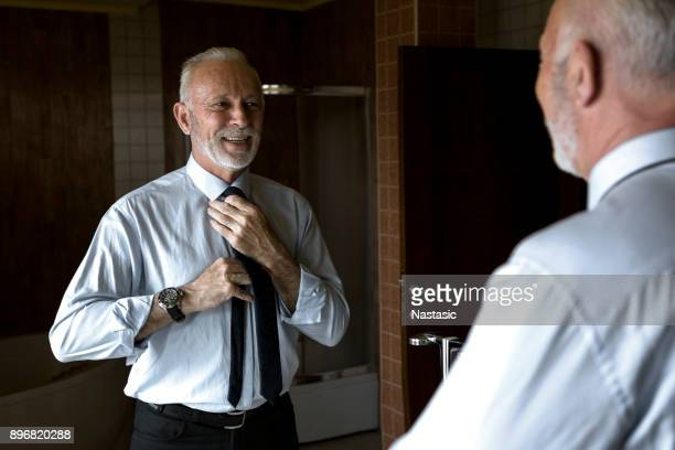 mature man looking in mirror - getting dressed stock pictures, royalty-free photos & images