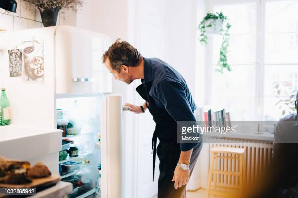 mature man looking into refrigerator while standing at kitchen - geladeira - fotografias e filmes do acervo