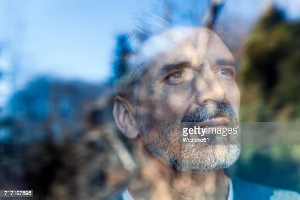 mature man looking out of window - imagination stock-fotos und bilder