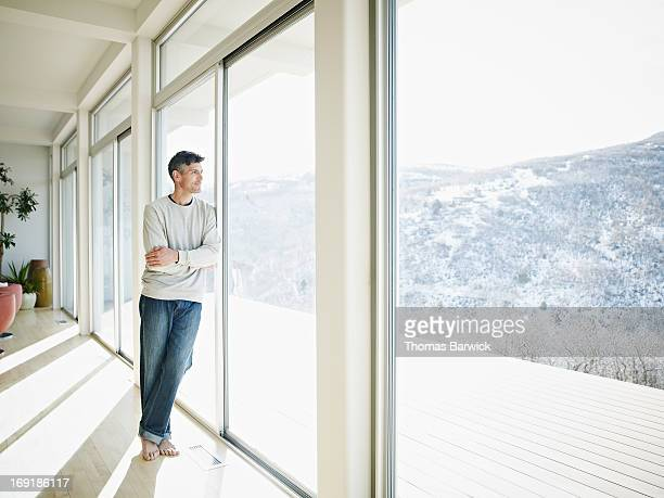 Mature man looking out windows of modern home