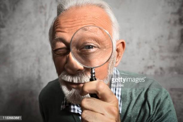 mature man looking through a magnifying glass - magnifying glass stock pictures, royalty-free photos & images