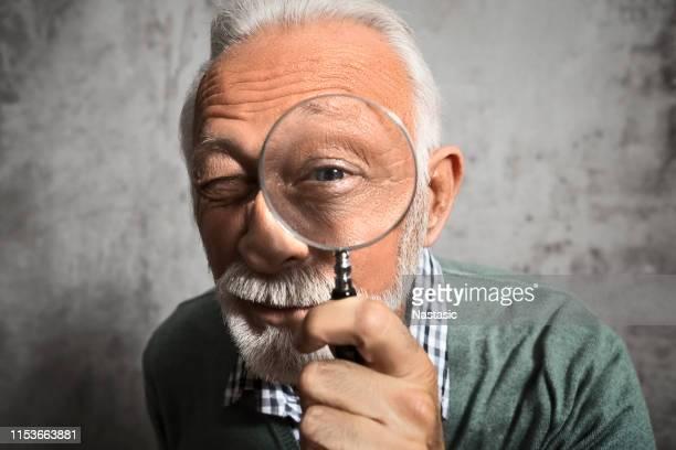虫眼鏡を通して見て成熟した男 - 虫メガネ ストックフォトと画像