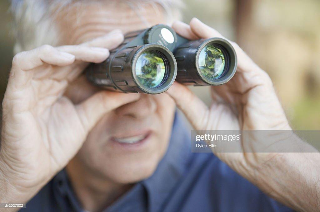 Mature Man Looking Through Binoculars : Stock Photo