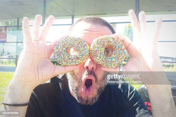 Mature Man Looking Through Donuts