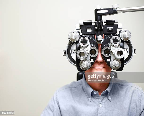 mature man looking through phoroptor - eye test equipment stock pictures, royalty-free photos & images