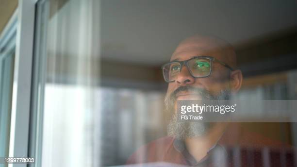 mature man looking through the window at home - resting stock pictures, royalty-free photos & images