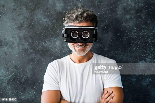 Mature man looking through VR glasses backwards