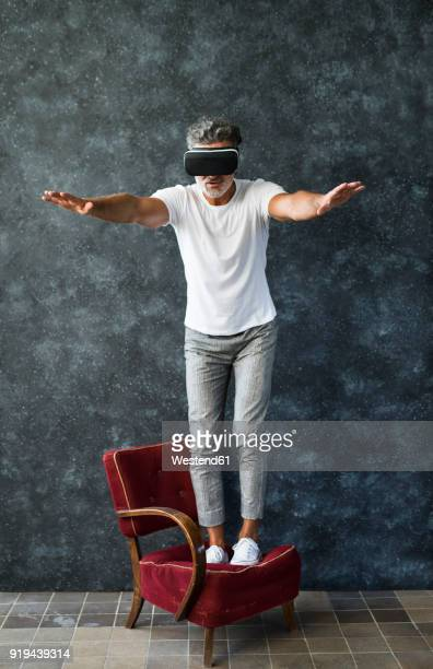 Mature man looking through VR glasses, balancing on armchair