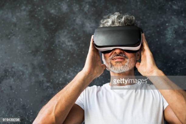 Mature man looking through VR glasses