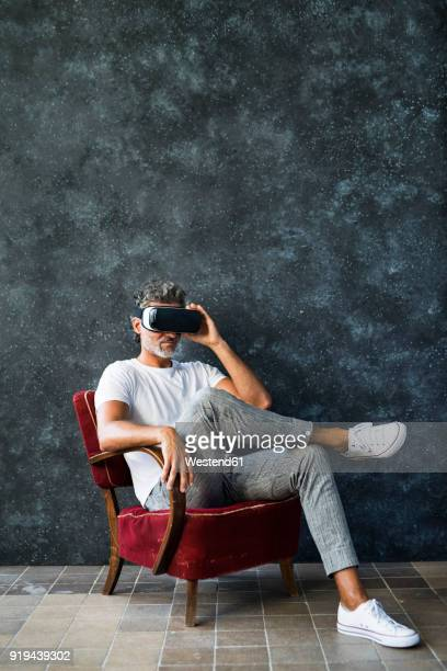 Mature man looking through VR glasses, sitting in armchair