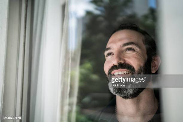 mature man looking through window at home - candid stock pictures, royalty-free photos & images