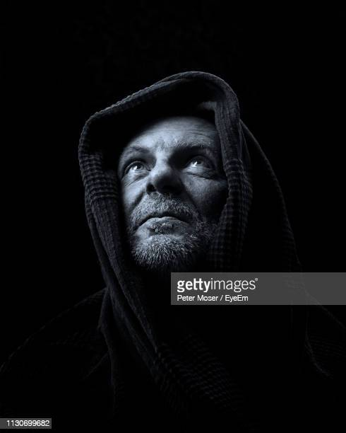 mature man looking up against black background - capucha fotografías e imágenes de stock
