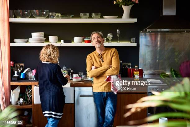 mature man looking up with arms folded with wife - husband stock pictures, royalty-free photos & images
