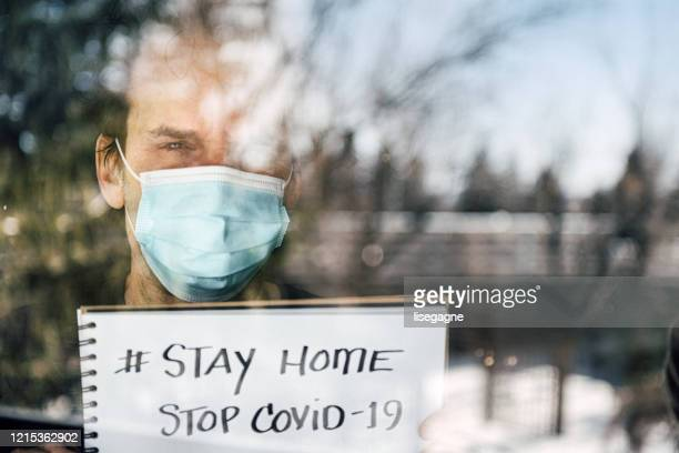 mature man lookoineg out through window during quarantine - stay at home order stock pictures, royalty-free photos & images