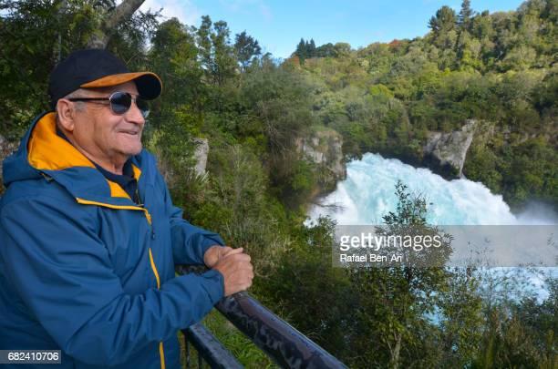 Mature man looks at Huka Falls New Zealand