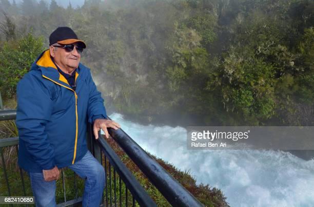 Mature man looks at rushing stream of Huka Falls New Zealand