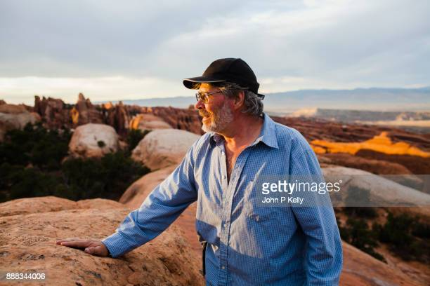 Mature man looks out at Canyonland National park in Utah.