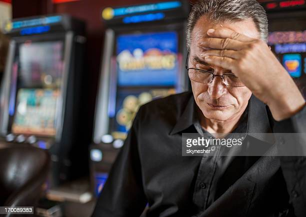 mature man loosing his money on slot machines. - defeat stock photos and pictures