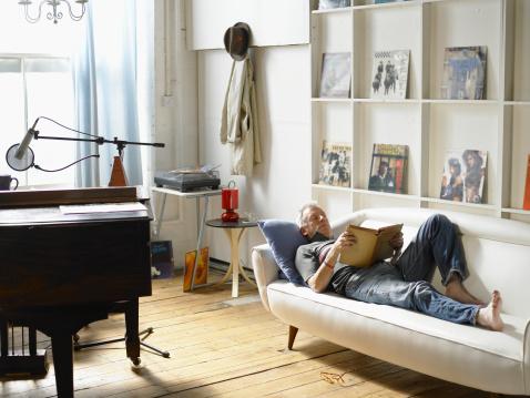 Mature man lying down, reading - gettyimageskorea