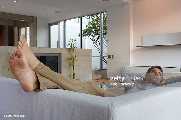 Mature man lying on couch