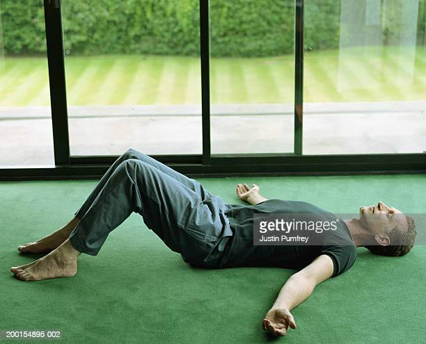 mature man lying on floor by large window, arms outstretched - lying on back stock pictures, royalty-free photos & images