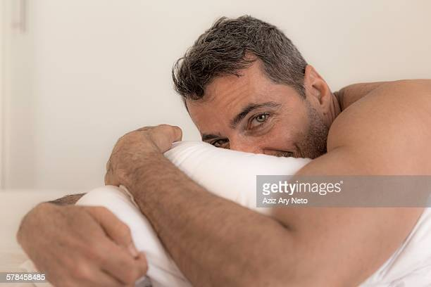 Mature man lying on front hugging pillow, looking at camera, face partially obscured