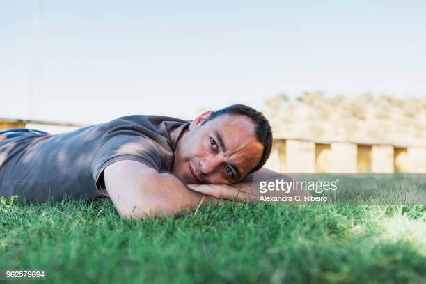 mature man lying on grass against clear sky - lying on front stock pictures, royalty-free photos & images
