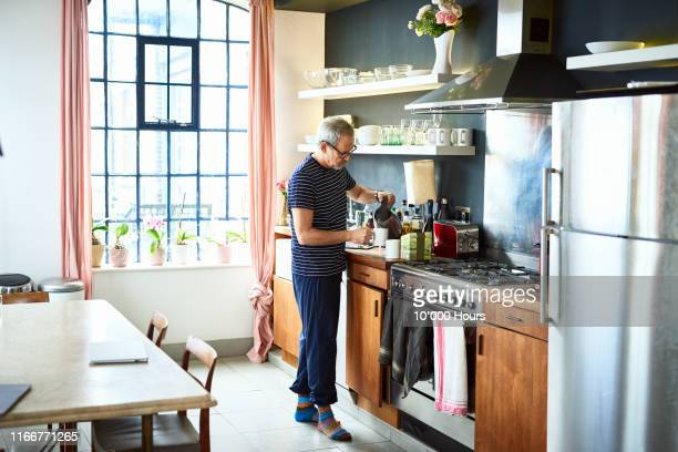 mature man making cup of tea at home in kitchen - making stock pictures, royalty-free photos & images