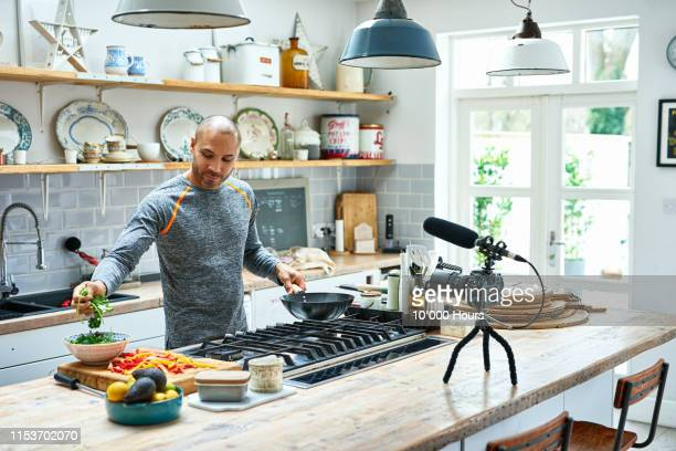 mature man making meal and using camcorder - performance stock pictures, royalty-free photos & images