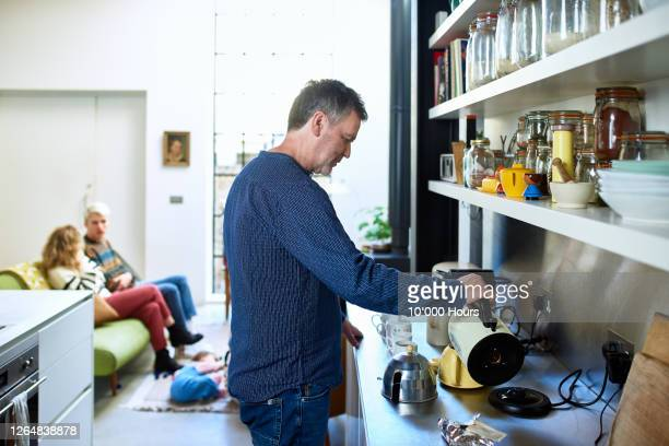 mature man making pot of tea in kitchen - making stock pictures, royalty-free photos & images