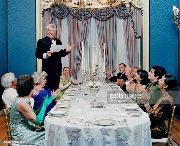 Mature man making speech at dinner party