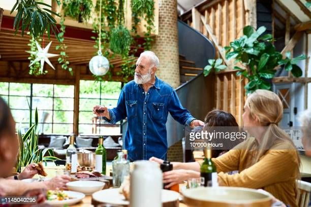 mature man making speech at dinner table with friends - speech stock pictures, royalty-free photos & images