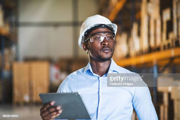 mature man manager or supervisor with clipboard in a warehouse. - casque de chantier photos et images de collection