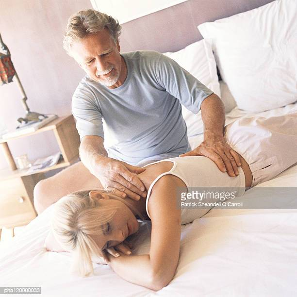 Mature man massaging woman on bed