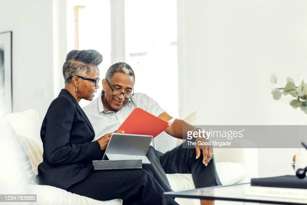 mature man meeting with financial advisor at home - financial occupation stock pictures, royalty-free photos & images