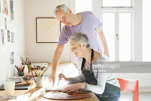 mature man mentoring woman in artist's studio - short hair stock pictures, royalty-free photos & images