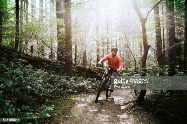 mature man mountain biking in forest - washington state stock pictures, royalty-free photos & images