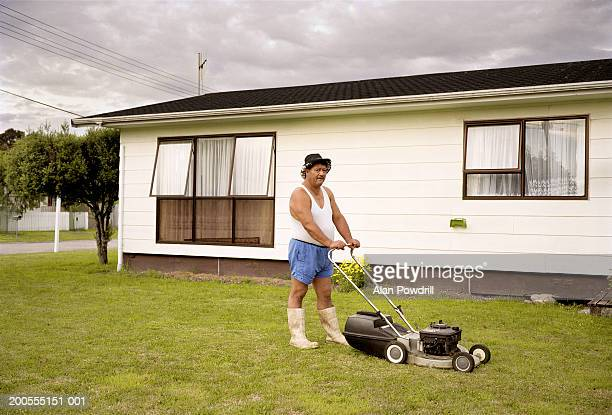 Mature man mowing grass outside house