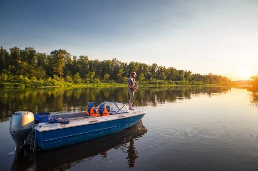 Mature man on a motor boat. Fishing. 618217102