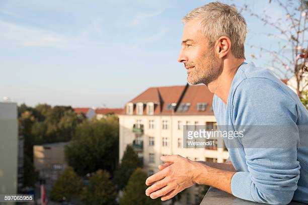 mature man on balcony, enjoying the view - handsome 50 year old men stock pictures, royalty-free photos & images