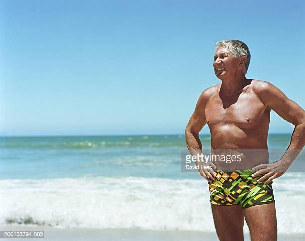 mature man on beach, hands on hips - calzoncini da bagno foto e immagini stock