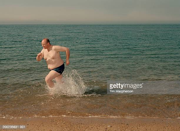 Mature man on beach running in surf