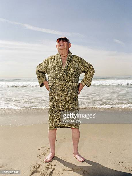 mature man on beach wearing sun glasses and leopard print robe - bathrobe stock pictures, royalty-free photos & images