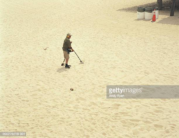 Mature man on beach with metal detector, elevated view