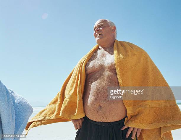 mature man on beach with towel around shoulders,  low angle view - wrapped in a towel stock pictures, royalty-free photos & images