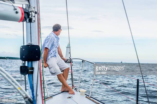 Mature man on bow of sailboat looking away towards lighthouse