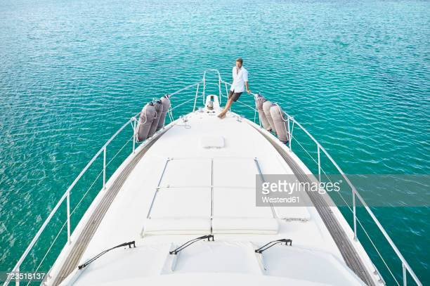 mature man on deck of his motor yacht - yacht de luxe photos et images de collection
