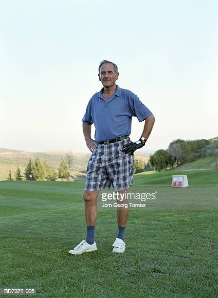 Mature man on golf course wearing checked shorts, portrait