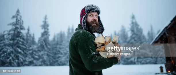 mature man on holiday in snowy winter nature, gathering firewood. - warm clothing stock pictures, royalty-free photos & images